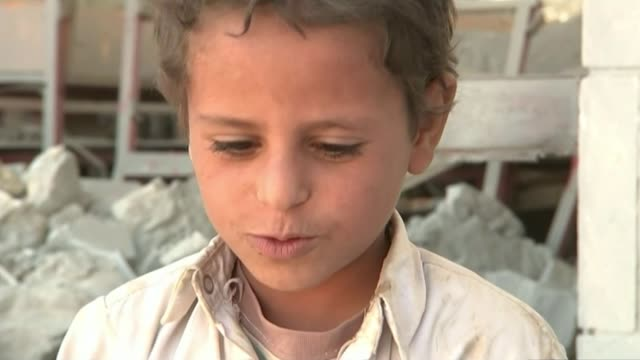 air strikes have devastating effect on civilians; yemen: ext woman walking along road past damaged structure tracking shot along past damaged... - 身体症状点の映像素材/bロール