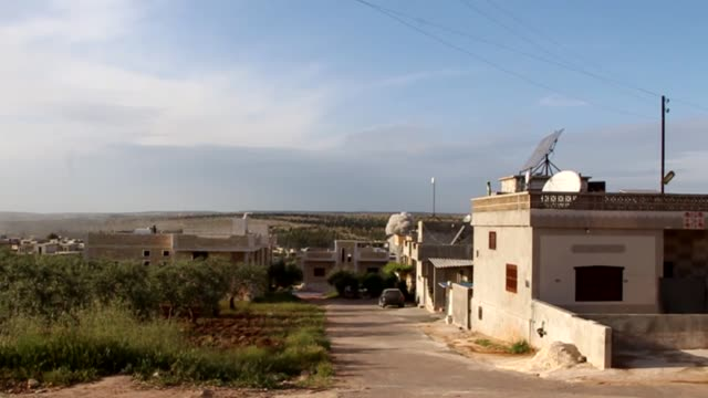Assad regime intensifies assault on last Syrian rebel enclave SYRIA Idlib EXT Smoke rises from distant building as hit by shell