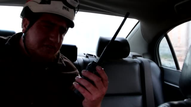 Assad regime intensifies assault on last Syrian rebel enclave SYRIA Idlib INT White Helmets rescue worker speaking on walkie talkie as along in back...