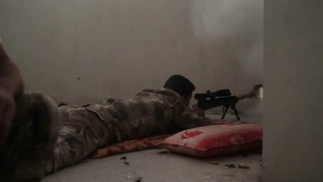 battle for mosul continues iraq mosul outskirts ext iraqi soldier lying on ground as aiming machine gun through small hole in wall iraqi soldier... - mosul stock videos and b-roll footage