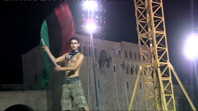 stockvideo's en b-roll-footage met battle for tripoli 2182011 green square green libyan flag hanging from balcony of building pull out rebel fighter waving red black and green flag of... - startvlag