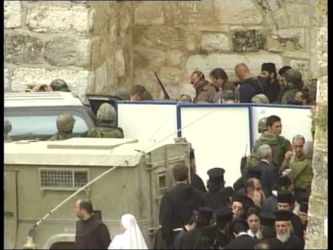 conflict bethlehem siege ends itn bethlehem tlms crowd of soldiers people gathered at door of church of the nativity as weapons removed after siege... - church of the nativity stock videos and b-roll footage