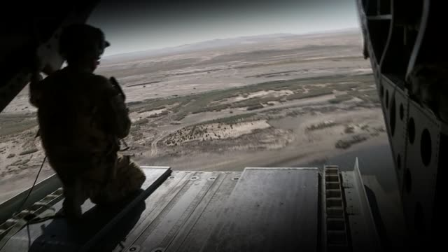 vídeos de stock e filmes b-roll de cabinet agrees 'on the need to take action' in syria t09101717 / tx afghanistan helmand province us soldier rear gunner seated at open doorway of... - helmand