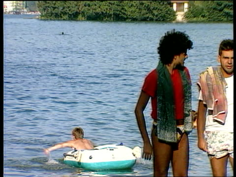 Civil war EXT Lake Bled TMS Boy paddling in inflatable raft OUT holidaymakers next water MS Man falling off windsurfer