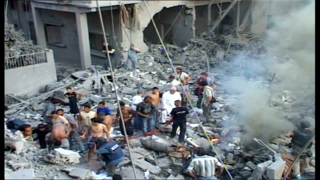vídeos de stock, filmes e b-roll de day 15 israeli jets continue attacks in the south lebanon tyre ext high angle shot of lebanese people climbing over smoking rubble of multistory... - tyre