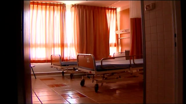 day 17 shelling of israel continues int back view of reporter along deserted hospital corridor with hospital director deserted hospital waiting room... - empty hospital waiting room stock videos & royalty-free footage