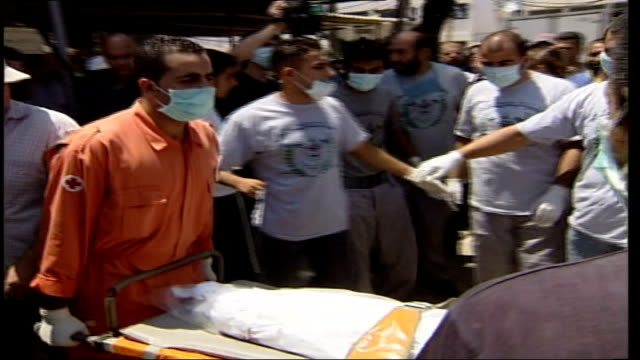 day 18 lebanese war victims buried in mass grave lebanon tyre ext red cross medics wearing protective breathing masks unloading dead body wrapped in... - mass grave stock videos and b-roll footage