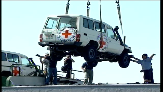 day 18 roundup lebanon beirut ext red cross ship carrying aid sails into port red cross jeep lifted by crane from ship large sacks containing red... - 赤十字社点の映像素材/bロール