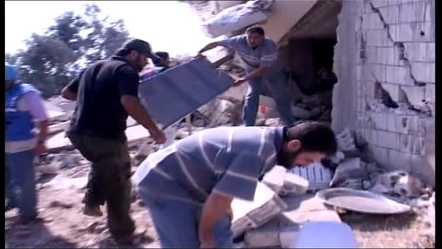 day 19 israel agrees to 48hour ceasefire lebanon qana ext line of bodies covered with sheets lying next rubble track forwards rescue workers carrying... - ceasefire stock videos and b-roll footage