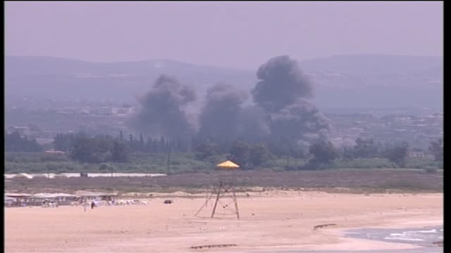 vídeos de stock, filmes e b-roll de day 24 southern lebanon red cross aid problems southern lebanon tyre ext long shot beach zoom in to black smoke from explosions rising behind - tyre