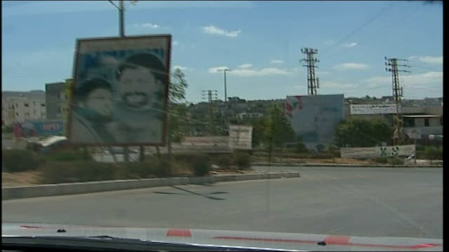 first day of ceasefire southern lebanon int car from car of hezbollah leader poster on roadside back view of reporter in car - hezbollah stock videos & royalty-free footage