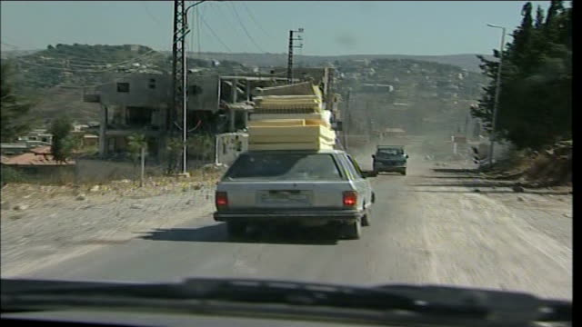 first day of ceasefire: southern lebanon; int car tracking shot behind car loaded with mattresses as approaching town of tibnin - ceasefire stock videos & royalty-free footage