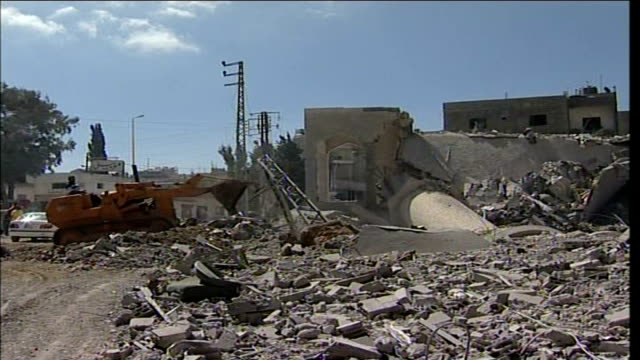 first day of ceasefire southern lebanon remains of bombed mosque and earthmover at work ambulance stranded beyond bomb crater rubble - ceasefire stock videos and b-roll footage