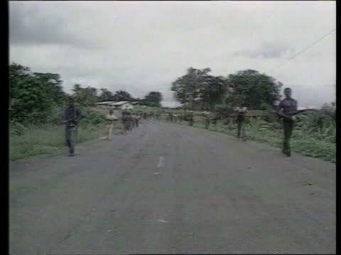 LIBERIA Monrovia Liberian rebels along road firing guns Crouching by roadside Refugees along past rebels Rebels on trucks Ellen JohnsonSirleaf White...