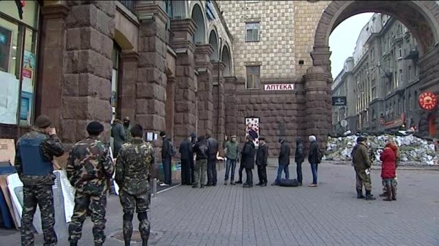 Interim government puts troops on full combat alert UKRAINE Kiev EXT General views of men queuing up outside building Arseniy Yatsenyuk along to...