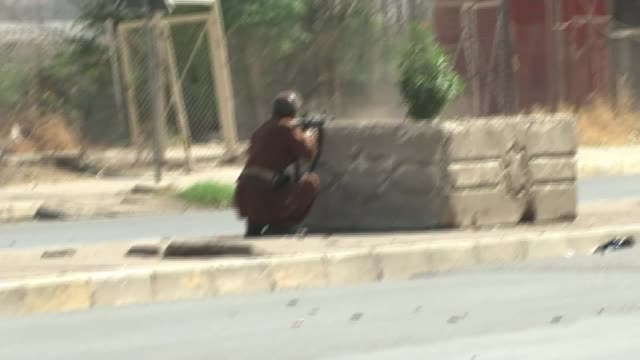 vídeos y material grabado en eventos de stock de islamic state militants launch attack on kirkuk; iraq: kirkuk: ext iraqi soldier crouches behing road bollard firing gun iraqi soldier fires machine... - channel 4 news