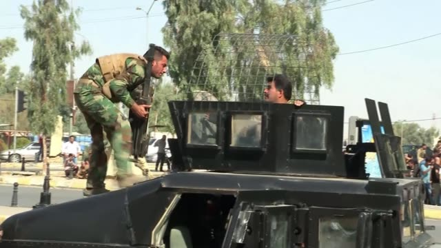 stockvideo's en b-roll-footage met islamic state militants launch attack on kirkuk; kurdish soldier helps lift grenade launcher onto military truck - channel 4 news