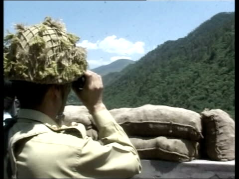 india/pakistan tension rises; lib sign warning of 'en posts' zoom in soldier in trench cbv soldier using binoculars to survey wooded hillside side... - zoom out点の映像素材/bロール