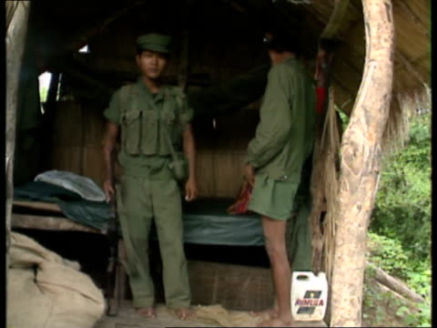 khmer rouge troops cambodia ext path through vegetation / huts on stilts / rocket propelled grenades leaning on hut / khmer rouge soldiers in camp /... - grass hut stock videos & royalty-free footage