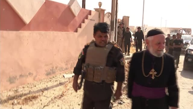 stockvideo's en b-roll-footage met kurdish forces retake bashiqa from islamic state as advance on mosul continues ninevah father john tarachee with wife salima tarachee ext tracking... - kerk