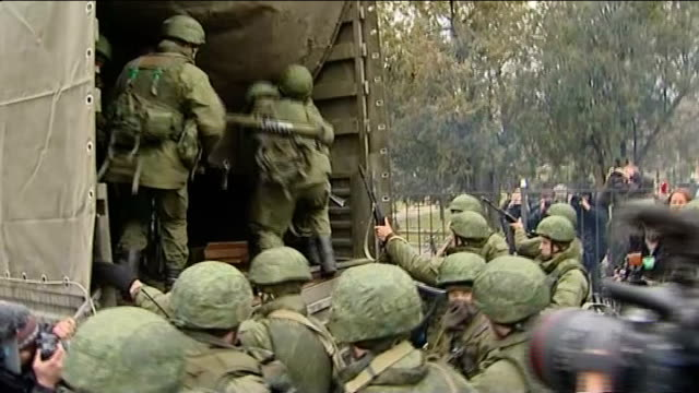 military build up in crimean peninsula / russia accused of 'armed invasion'; ukraine: crimea: ext various of armed troops / soldiers board military... - ウクライナ点の映像素材/bロール