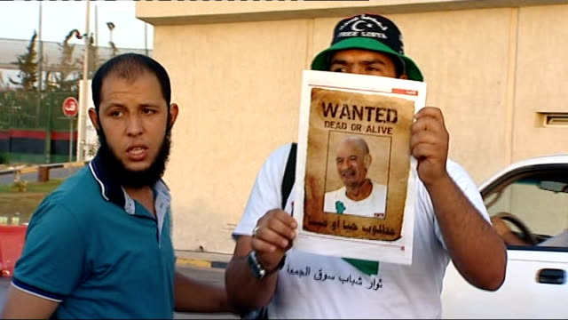 military pressure on gaddafi family intensifies ext libyan man holding up poster showing member of gaddafi family and heading wanted dead or alive - poster stock videos & royalty-free footage