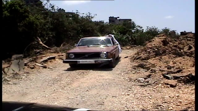 more violence as israeli forces cross border tyre ext cars along on uneven road pan bomb crater at roadside - uneven stock videos & royalty-free footage