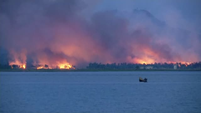 stockvideo's en b-roll-footage met new wave of rohingya refugees flock to bangladesh camps; lib 14.9.2017 bangladesh / myanmar border: night wide shots of flames and smoke from burning... - channel 4 news
