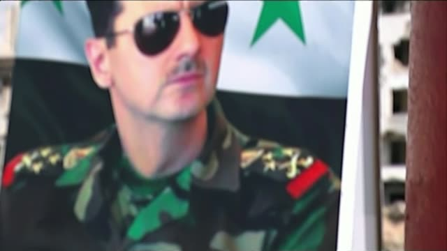 options for the fight against resilient islamic state militants t16031519 / syria homs al waer ext man painting syrian flag on wall pan to poster of... - バッシャール・アル=アサド点の映像素材/bロール