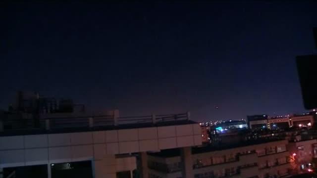 vidéos et rushes de palestinian rocket attack on tel aviv israel tel aviv gvs night sky over city buildings as bomb siren heard sot gv missiles along in night sky and... - israël