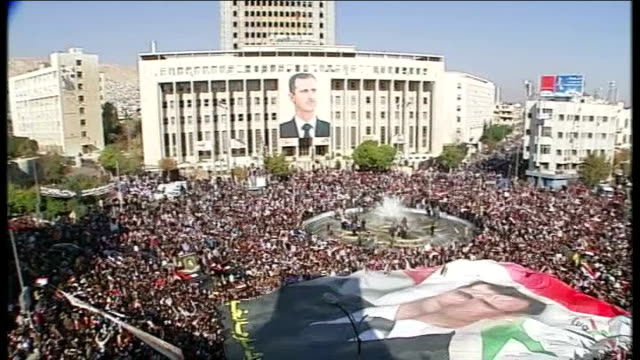 photographs allegedly show evidence of mass torture and killing of detainees; lib syria: damascus: ext high angle shot of massed crowd gathered at... - torture stock videos & royalty-free footage