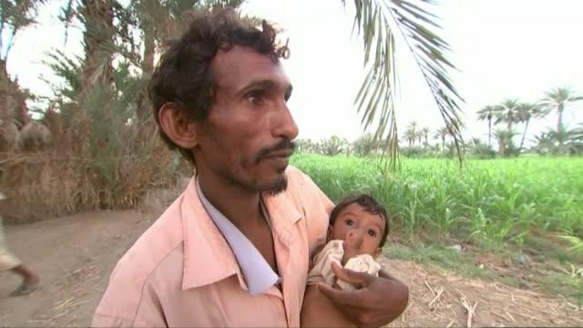 population face threat of starvation as food imports are disrupted yemen ext various of reporter talking to man holding malnourished child villagers... - yemen bildbanksvideor och videomaterial från bakom kulisserna