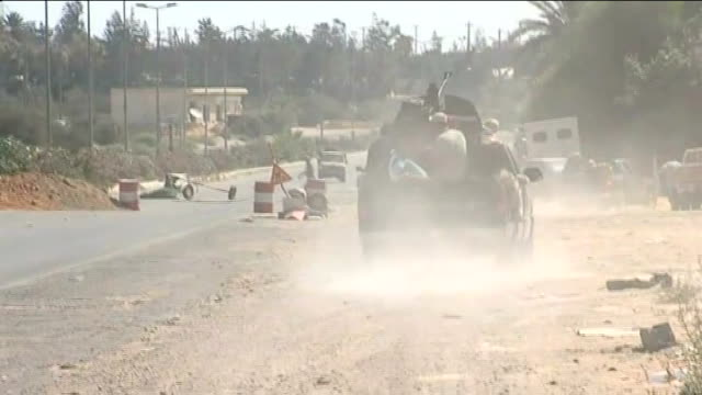 stockvideo's en b-roll-footage met rebel forces take tripoli; libya: tripoli: ext wide shot rebel army vehicles in road as artillery fired during battle with pro-gaddafi forces sot... - war and conflict