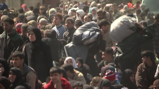 refugees flee eastern ghouta as government recapture territory syria eastern ghouta ext wide shot crowd of syrian refugees pan woman in headscarf... - exile stock videos & royalty-free footage