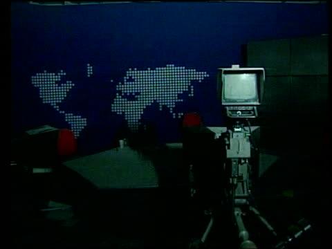 vídeos de stock e filmes b-roll de serbian tv station bombed itn cameras in empty newsroom studio control room of studio tilt down hose jet trained on smouldering area la plume of... - sérvia