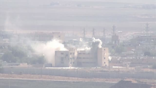 turkey's syria offensive: kurdish forces accept support from syrian president bashar al-assad; syria: ext smoke rising as bombs hit buildings in... - クルド人点の映像素材/bロール