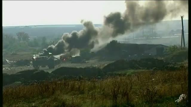 vídeos de stock e filmes b-roll de ukrainian troops on the retreat; burning armoured vehicle at ukrainian army camp hit by rocket fire smoke rising from vehicle at ukrainian camp close... - ucrânia bandeira