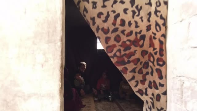 stockvideo's en b-roll-footage met calls for ceasefire as children die in freezing conditions; syria: idlib: tent int tracking shot along inside of tent to room to show family sat on... - war and conflict
