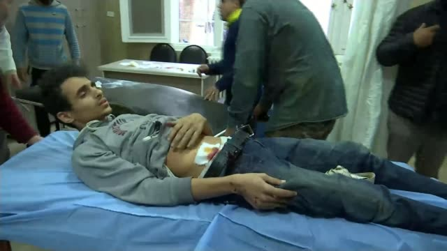 un condemns both sides in syrian civil war for targeting hospitals and civilians t03111612 / tx syria aleppo ext ambulance arriving injured man on... - シリア点の映像素材/bロール