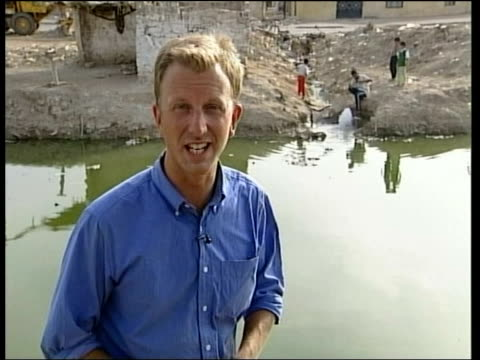vídeos y material grabado en eventos de stock de cholera fears evening news philip reay smith itn iraq basra people along rubbish covered street pan dirty rubbish filled canal rubbish floating in... - basra