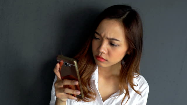 Confused, Angry, Anxious Woman using smartphone