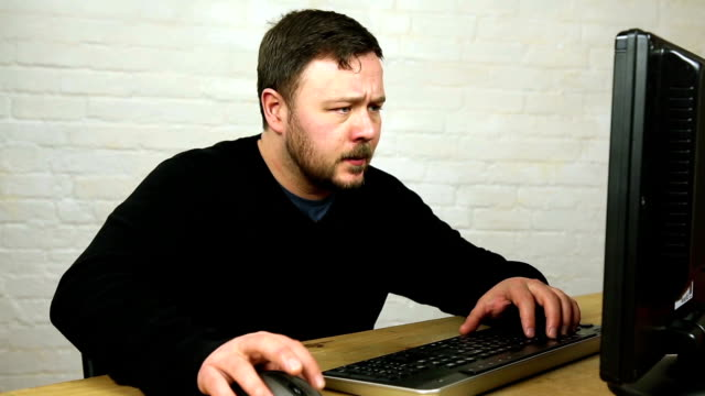 confused angry man typing on keyboard in front of computer