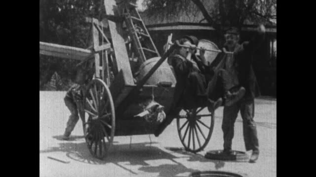1915 confused boss struggles to get supply cart moving again after exhausted charlie chaplin falls in manhole - horse cart stock videos and b-roll footage