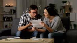 Confused couple reading a letter in the night