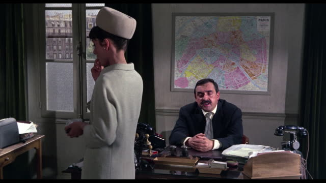 1963 Confused detective (Jacques Marin) questions woman (Audrey Hepburn)