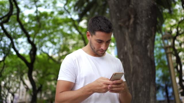 turista maschio confuso in cerca di direzione sul suo cellulare - public park video stock e b–roll