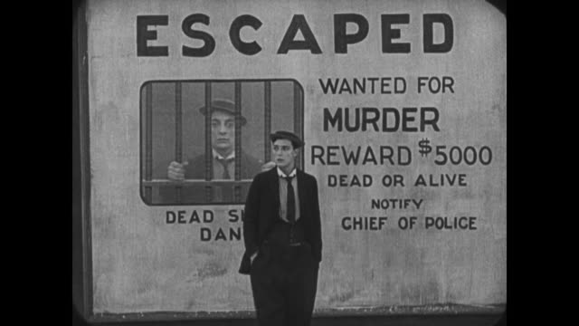 1921 Confused man (Buster Keaton) frightens passersby in case of mistaken identity before seeing his face on wanted poster