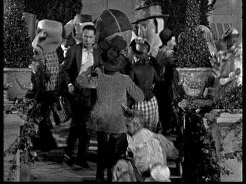 1925 ms b/w confused man looking around on costume party in garden at night - 1925 stock videos & royalty-free footage
