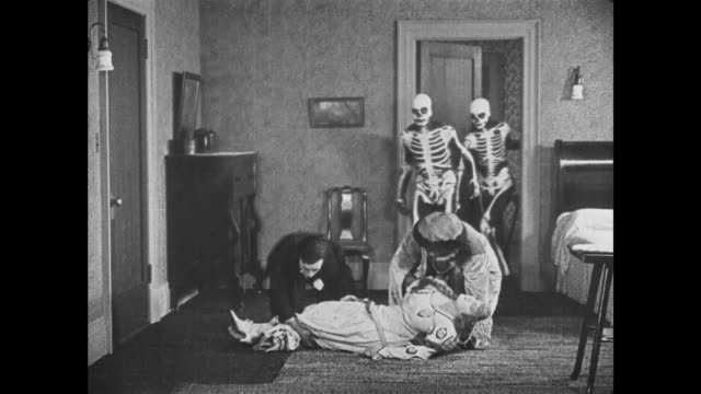 1921 Confused man (Buster Keaton) tries to aid costumed man in lifting woman but runs away when two skeletons show up to help