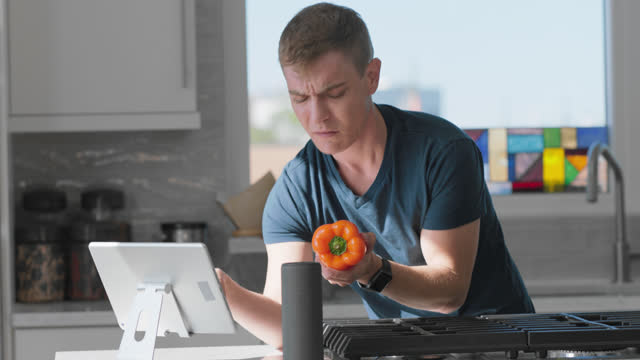 confused man tries to figure out what to do with a vegetable in his kitchen - wrist watch stock videos & royalty-free footage